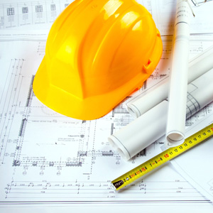 Building design schematics with hardhat and tape measure